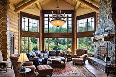 Rocky Mountain Log Homes  Love this room--would do a little different rock on the fireplace.  Love the chandelier though--thank goodness it is not another overdone and tacky antler chandelier--so tired of seeing those hideous things in every design idea for log homes.