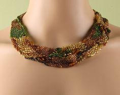 This necklace captures the colors of fall, with varied shades of gold and green. It is beautifully textured with lampwork glass beads, crystal