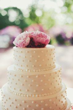 Torta de boda de tres niveles en círculos, glaseado de color blanco, punticos blancos y adornada con peonias en la parte superior de color rosa. #TortasDeBodas #DecoracionBodas