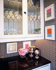White cabinets with leaded glass fronts paired with black-and-white patterned wallpaper