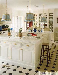 """Homeowner and interior designer Anne Miller uses both islands as seating areas at kitchen dinner parties. """"The built-in breakfront was designed to look like a piece of furniture, with glass fronts and mirror-backed cabinets to reflect the glassware,"""" she says.   - HouseBeautiful.com"""