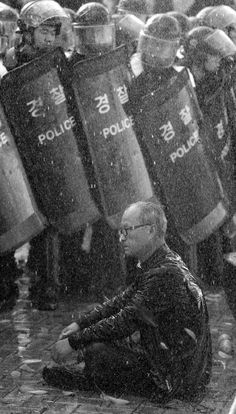 A protester sits in front of riot police as the police use water cannon to disperse a rally against the South Korea-US free trade agreement talks in Seoul. 3 November 2011