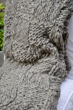 The 'Malena Grey Throw' is a fluffy & richly textured cable knitted wool throw. A 'must' piece, if you want to décor your home with a trendy & chic look. 100% natural grey wool - Handknitted