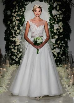 Floral-inspired cutouts and a sheer bodice are paired with an A-line silhouette to keep things classic in this Anne Barge wedding dress.