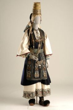 Ενδυμασία Νομάδων Πίνδου 19ος – 20ός αι.Η ενδυμασία φοριόταν από τους Αρβανιτόβλαχους που ονομάζονταν Καραγκούνηδες της Ηπείρου. Αποτελείται από λευκό πουκάμισο με κέντημα στον ποδόγυρο και την τραχηλιά, μαύρο σεγκούνι και υφαντή ποδιά. Στο κεφάλι φορούν πρόσθετες κοτσίδες ενώ ο κεφαλόδεσμος αποτελείται από ψηλό κωνοειδές καπέλο που τη βάση του περιτρέχει ασημένιο έλασμα, ως διάδημα. Οι ασημένιες αλυσίδες στο στήθος, η ζώνη με την πόρπη, το κεμέρι, και τα βραχιόλια συμπληρώνουν τη φορεσιά.