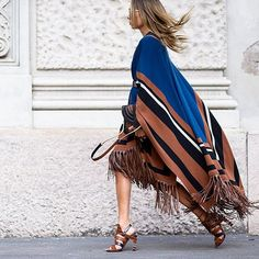 A fringed cape is the ultimate coverup for #fall. Coordinate accessories for added polish. #MFW #streetstyle by theurbanspotter