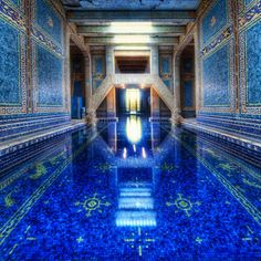 The Roman Pool at Hearst castle is a tiled indoor pool decorated with eight statues of Roman gods, goddesses and heroes. The pool appears to be styled after an ancient Roman bath such as the Baths of Caracalla in Rome c. 211-17 CE. The mosaic tiled patterns were inspired by mosaics found in the 5th Century Mausoleum of Galla Placidia in Ravenna, Italy.