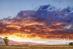 An epic Colorado sunset with the clouds on fire with blue sky above and the sun giving light to a country landscape and view of the Rocky Mountain foothills. Fine art photography prints, decorative canvas prints, acrylic prints, metal print wall art for sale on FineArtAmerica.com. Prints starting at $22. Copyright: James Bo Insogna