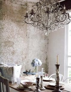 Dream dining room. Chandelier, tall candel holders, wrought iron, brick wall