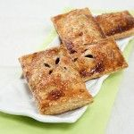 Blackberry Hand Pies displayed in a row on rectangle-shaped, white textured serving dish.