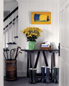 Mud Room or Stairwell with White Wood Paneling, Umbrella Stand, & Dark Wood Table. Green & Yellow Accents (Scott Sanders)