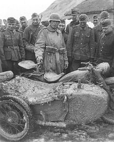 A large group of soldiers gathering around a driver and his Zundapp KS 750 with side car