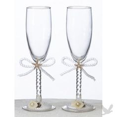 """A white cording bow and seashells help accent this pair of toasting glasses.  Each glass measures 8"""" tall.  Decoration is removable."""