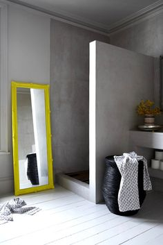 a minimalist concrete shower punched with a yellow floor mirror. pop of color