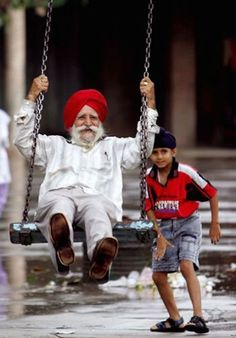 Never too old to be young at heart! child pushing india man in red turban in swing playing