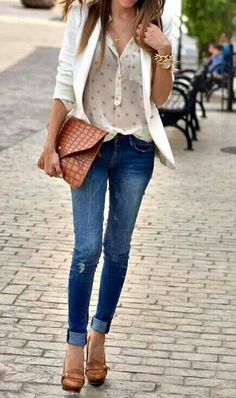 25 Stylish Outfits With Cuffed Jeans: Woman on the streets of the city in blue cuffed skinny jeans with a loose silk shirt and white blazer