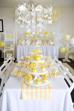 Yellow  White High Tea Party- The main seating table is beautifully decorated with a yellow and white striped table runner, a white antique bird cage as the centerpiece and lovely yellow flowers arranged in white containers. Cupcakes with matching wrappers and flags were displayed on simple white cake stands and the white paper butterfly chandelier is the perfect accent. #Cake