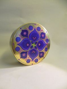 Vintage IRA cookie jar designed by Anita Wangel. The jar has a golden background color and purple, blue, pink and green flower decoration.    The