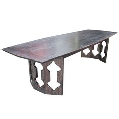 This unique, mid-century modern coffee table features a dark stain with a cerused finish showcasing the highly-figured wood grain. The Moorish-inspired motif repeated on the legs is similar to the designs of Harvey Probber from this period.