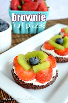 Mini brownies topped with frosting and fresh fruit.  No one can every resist these!