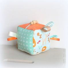 This sensory cloth block is designed for babies. Each side has textures and prints to enhance your babys senses, including: wooden beads that can be moved back and forth, a side that crinkles when touched, and bright colored ribbons to grab a hold of.  This block is approximately 4 1/2 inches square.  All products ship from my pet and smoke free home