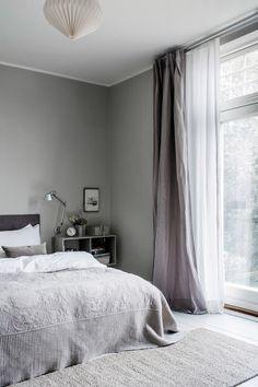 Makuuhuoneen sisustus on zen, kiitos harmaan eri sävyjen. Taftiverhot ja matto ovat tanskalaismerkki Tine K Homelta, jota myy Suomessa moni sisustusliike.