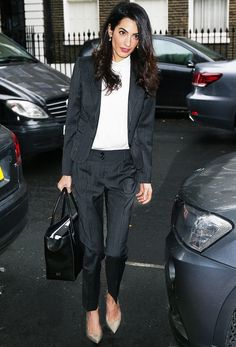 Amal Clooney pairs a pinstripe suit with a white blouse and nude pumps.