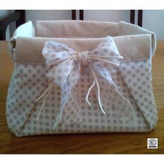 Con la tecnica origami nasce questo cestino un po' chic e un po' shabby, realizzato in doppio tessuto 100% e decorato con un fiocchetto in tinta. Dimensioni cm. 16 x 16 ca.
