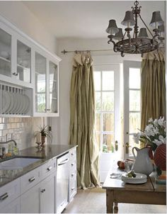 French Style - Karyl Pierce Paxton - New Orleans Cottage - White kitchen with a Louisiana wood table and soft drapes dressing the French doors. French Door Curtains, French Doors, Burlap Curtains, Hanging Curtains, Drapes Curtains, Shabby Chic Kitchen, Kitchen Decor, Kitchen Ideas, Rustic Kitchen