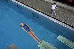 A member of Crystal Palace diving club dives watched by coach Xiang Yan Kong during a training session in London March 9, 2012.  REUTERS/Stefan Wermuth