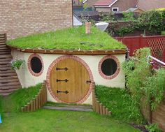 Love the circular door and green roof, plus those interesting wings flanking the door. From the Green Roofing Tumblr site.