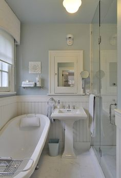 Small bathroom made to seem bigger by using pale blue and white and glass door to shower. By Bilton Design Group, Calgary.