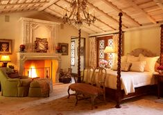This bedroom's nine-foot-tall  four-poster bed was designed to get the height needed for the vaulted space.  The commanding antique mantel and chimney hearth also add verticality. The  cosmetic-like palette of creams, peaches, and rosy pinks was chosen for is  ability to flatter. A plush armchair and ottoman provide a cozy spot for  reading and relaxing by the fire.
