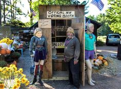 In this Sept. 29, 2016 photo, Chris Owens stands beside his outhouse-turned-voting booth at Owens Truck Farm in Ashland, N.H. Manikins of presidential candidates Hillary Clinton and Donald Trump hang outside the booth, while ballots are deposited into side-by-side toilets inside the booth. (Sean Hurley/New Hampshire Public Radio via AP)