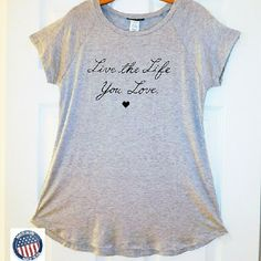 """Live the Life  You Love"" Long T-shirt Long and loose fitting with raglan style sleeves.  Scoop neck.  Shirttail hem, slightly longer in back.  Approx. 28"" long.    95% Rayon/5% Spandex.  Hand Wash.  Made in the USA. Boutique Tops Tees - Short Sleeve"