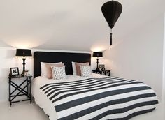 Black and white master bedroom: white floors. Stripes. Lamps.