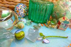Any combination of these items could be a still life set-up.  There's a couple fluorite octahedrons (8 sided aqua-colored crystals), a few artsy marbles, a clear glass paperweight, an ornate Italian bottle cork, a green votive, some beach pebbles, a basket, a papier mache globe covered with pieces of maps, a little wooden house covered with pretty patterned paper, some citron beads and watch parts beaded together with a marble in the center, and a beaded heart-shaped flower with stem and…