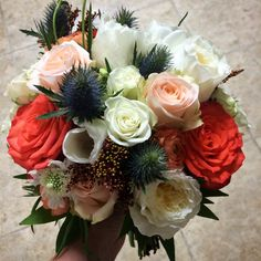 Funky tropical bouquet with peach, blue and white blooms of roses, garden roses, tulips, scabiosa, thistle, solidago, ranunculus, and spray roses with accent foliage