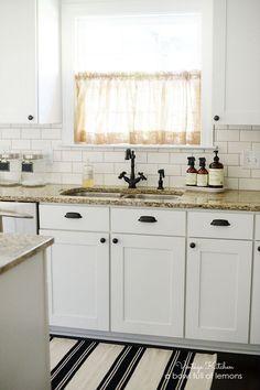 white kitchen kabinets with granite countertops, subway tile, and ikea rug