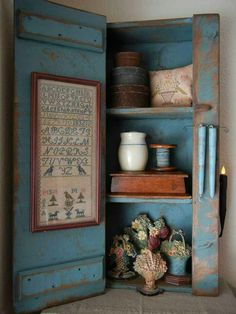 CUPBOARD IN BLUE PAINT FILLED WITH PRIMITIVES AND A FRAMED SAMPLER ON THE DOOR.