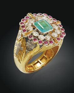 A FRENCH BISHOP'S RING, MAKER'S MARK MP, Mr. PECHOUX POSSIBLY PARIS, CIRCA 1900 GOLD, PLATINUM, EMERALD, DIAMOND, RUBIES AND CITRINE a centered rectangular emerald cut sides in a circular openwork diamonds and rubies, citrines enhanced calibrated, the frame decorated with crosses and flowers platinum and carved foliage and flowers against mandorle