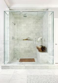 Pretty marble bathroom tile with glass door, bench, wall ledge, regular shower head and rain shower head