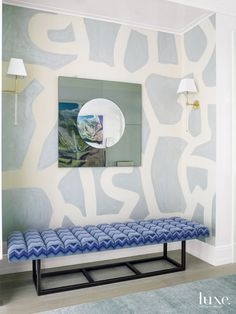 A matte, hand-painted wallcovering on Japanese paper by Porter Teleo gives definition to a niche in the lacquered foyer. The custom bench, Circle in Square mirror and The Urban Electric Co. sconces were purchased through designer Chris Desmone's studio, HB Home NYC.