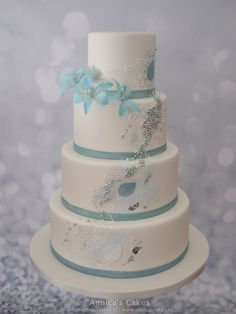 Moderne bruidstaart zilver en licht blauwe accenten en licht blauwe orchideeën.