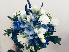 Blue and white bouquet, with a hint of deep purple. Blue hydrangea, bachelor's button, white freesia, carnations, and purple veronica.