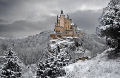 The Alcazar of Segovia in winter.  The Alcázar of Segovia is a stone fortification, located in the old city of Segovia, Spain. It is one of the most distinctive castle-palaces in Spain by virtue of its shape – like the bow of a ship. The Alcázar was originally built as a fortress but has served as a royal palace, a state prison, a Royal Artillery College and a military academy since then. The castle is one of the inspirations for Walt Disney's Cinderella Castle.