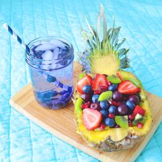 Pineapple fruit bowl with strawberries, blueberries, kiwifruit, grapes, and pomegranate with berry infused water!