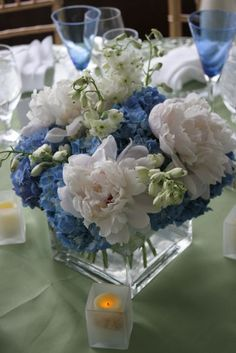 A table centrepiece with blue hydrangeas delphiniums and white peonies reception wedding flowers,  wedding decor, wedding flower centerpiece, wedding flower arrangement, add pic source on comment and we will update it. www.myfloweraffair.com can create this beautiful wedding flower look.