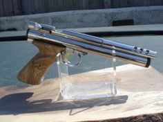 Crossman 2240 pistol with 2250 main value and CO2 tube. Highly polished pistol frame, hand crafted Oak grips, Nickel plated CO2 tube, Nickel plated Steel Breech. Nickel plated 3 vent custom barrel shroud.