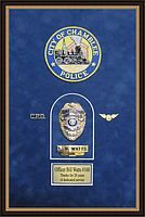 Police Department retirement shadow box with police badges, patches, ID cards and lapel pins.